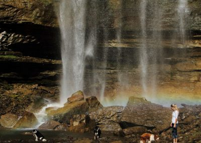 waterfall-rainbow-woman-dogs